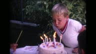 1964 boy blowing out birthday candles
