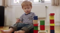 A boy building a tower using toy bricks Sweden.