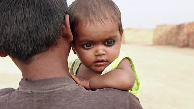Boy carrying his brother, Haryana, India