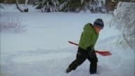 MS, PAN, Boy (6-7) carrying shovel, walking through snow, Yarmouth, Maine, USA