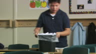 boy cleaning up trash in the classroom
