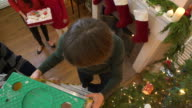 Boy climbing a ladder to decorate a Christmas tree