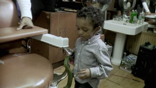 MS TU Boy (2-3) climbing onto barber chair, barber standing behind chair, Brooklyn, New York City, New York State, USA