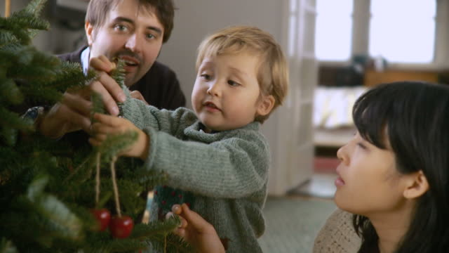 CU R/F Boy (2-3) decorating Christmas tree, father and mother clapping hands / New York City, New York, USA