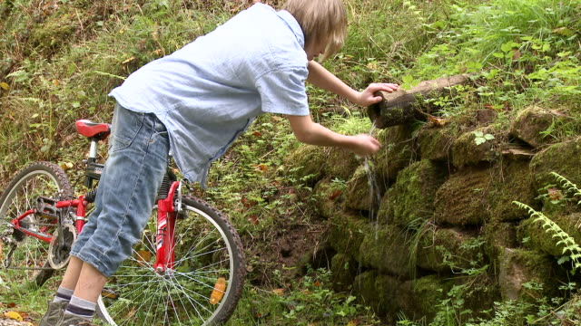 WS Boy drinking water with bicycle at forest / Tawern, Rhineland-Palatinate, Germany