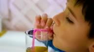 boy drinks juice through a straw