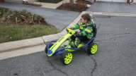 Boy driving gocart comes out of driveway and turns onto residential street.