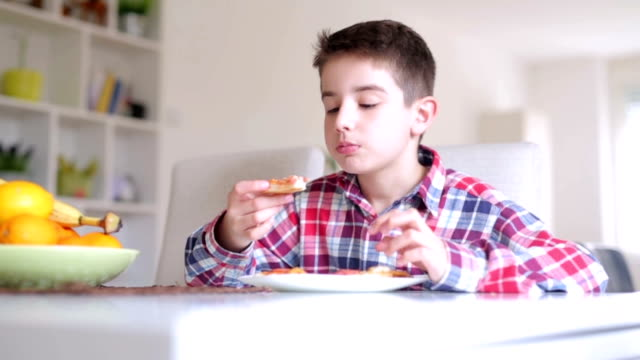Boy eating pizza at home