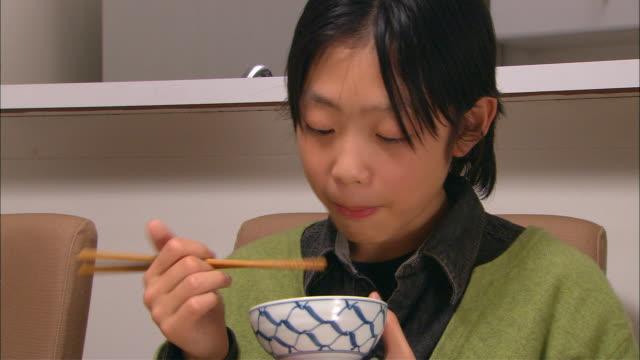 CU, Boy (10-11) eating traditional Japanese dinner