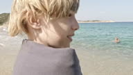 Boy enjoying on the beach, smiling at camera