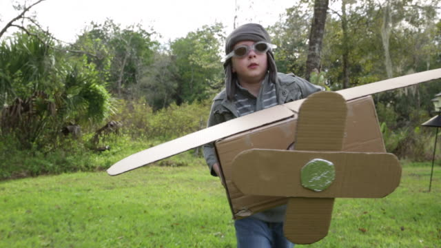 TS boy flying cardboard aeroplane towards camera dressed as pilot.