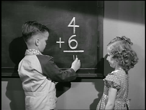 B/W 1949 boy + girl at chalkboard doing addition problem / girl corrects boy's mistake / industrial