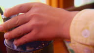 Boy grabbing tubes of paint from jar, extreme close up