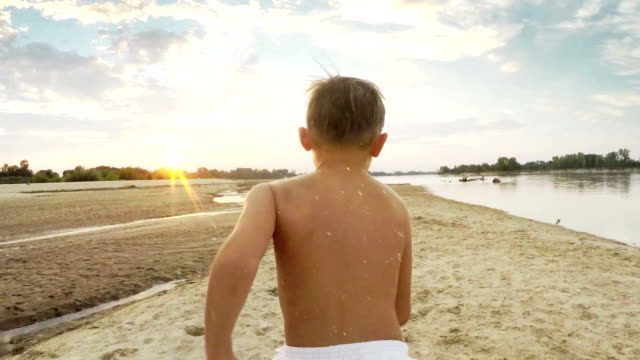 Boy having fun. Race along the shore