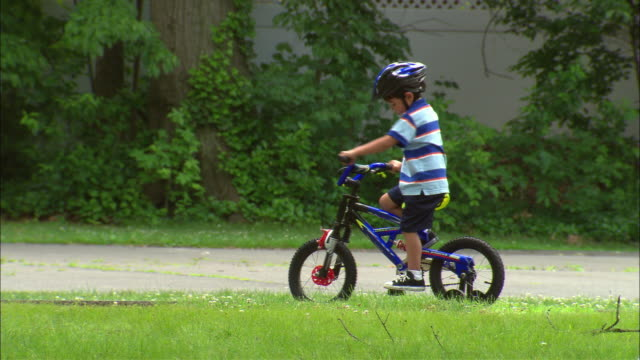 WS Boy having trouble getting started while trying to ride his bicycle/ Mother arriving to give bike a push/ Boy briefly riding alongside girl on bike before coming to a stop/ Fanwood, New Jersey