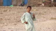 MS TS TU Boy holding books and walking in village / Egypt