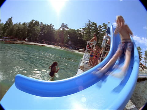 FISHEYE boy holding nose + giving peace sign going down slide into lake surrounded by pine trees