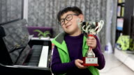 boy holding silver medal cup by the piano