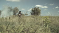Boy in a costume with artificial wings walking through field, tracking shot