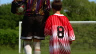 A boy in an over sized soccer jersey holds hands with another soccer player.
