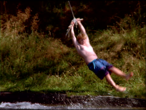 Boy in blue swimming trunks swings on rope over water, Norway