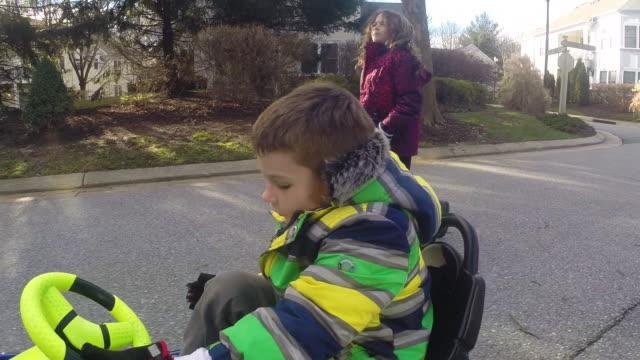 Boy in go-cart drives down residential street at sunset as girl jogs alongside.