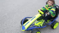 Boy in gocart rides down residential street as oncoming car waits for him to pass.