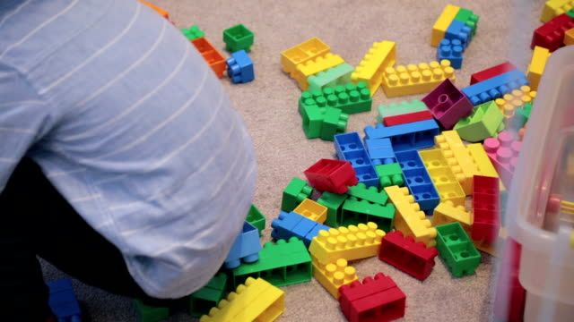 Boy in kindergarten playing with toy blocks