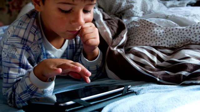 Junge im Schlafanzug im Bett und spielt auf einer Platte