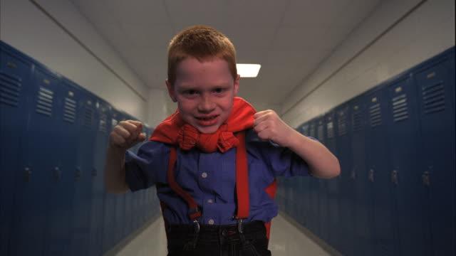 MS DS REAR POV Boy (5-6) in school corridor, striking hero pose, Oshkosh, Wisconsin, USA