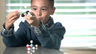 Boy in science class talking about molecule model