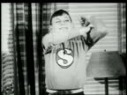 1948 TD boy in superhero costume posing and flexing in living room / United States
