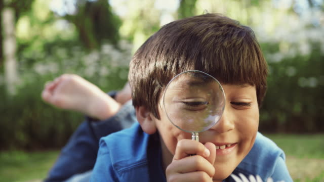 CU Boy (8-9) inspecting flower with magnifying glass / Seattle, Washington, USA