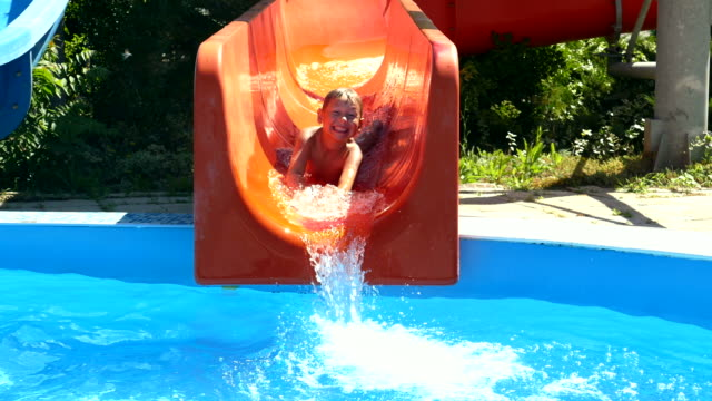 boy is riding the water slides