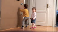 Boy is running around little toddler girl and playing