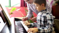 Boy learning the piano with her teacher