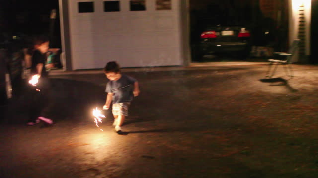 WS PAN Boy (4-5) lighting sparklers on 4th of July / Lovell, Maine, USA