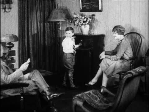 B/W 1924 boy listening to radio as parents sit by in living room / newsreel