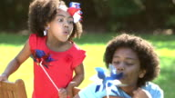 Boy, little sister playing with red, white and blue pinwheels