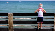 boy looking over the fence by the sea