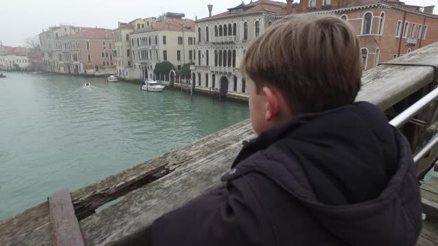 Boy looking over Venice Bridge