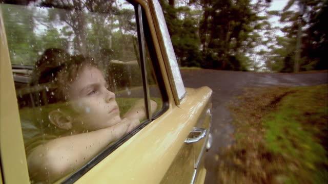 CU, Boy (6-7) looking through car window in rain, Tamborine Mountain, Brisbane, Queensland, Australia