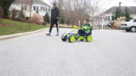 Boy meanders down a residential road in his gocart as his father walks behind him.