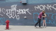 MS PAN Boy on his skateboard meets girl and walking together in street / Montreal, Quebec, Canada