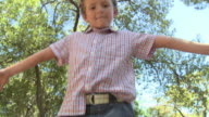 Boy on log, standing on one leg and walking