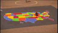 HA WS boy on playground filling in states with different colors on outline map of US/ boy leaving/ Michigan