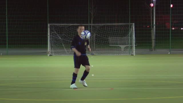 WS Boy (14-15) on soccer field doing keep-ups, London, UK
