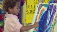 MS TD Boy painting on easel in preschool classroom / San Antonio, Texas, USA