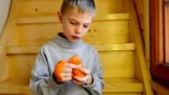 Junge peeling mit Mandarine
