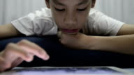 Boy playing digital tablet